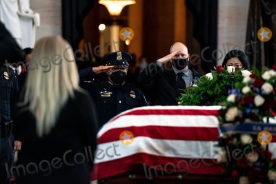 Photo - United States Capitol Police officer Ken Shaver who was also injured in the April 2nd  attack at the Capitol center raises his hand in salute to the late US Capitol Police officer William Billy Evans as he lies in honor in the Rotunda of the US Capitol in Washington DC on April 13th 2020Credit Anna Moneymaker  Pool via CNPAdMedia