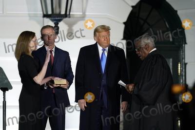 CLARENCE THOMAS Photo - Associate Justice of the Supreme Court Clarence Thomas administers the oath of office to Judge Amy Coney Barrett to be Associate Justice of the Supreme Court on the South Lawn of the White House in Washington DC on Monday October 26 2020  US President Donald J Trump and her husband Jesse M Barrett look onCredit Chris Kleponis  Pool via CNPAdMedia