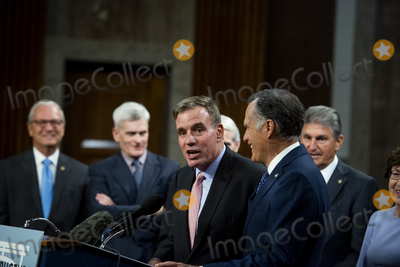 Photo - United States Senator Mark Warner (Democrat of Virginia) left is embraced by United States Senator Mitt Romney (Republican of Utah) as he makes remarks after the vote on the motion to invoke cloture to proceed to the consideration of HR 3684 the INVEST in America Act on Capitol Hill in Washington DC on Wednesday July 28 2021 The vote to begin discussion of the bipartisan infrastructure bill agreed to by the White House was 67 to 32 If passed the bill would invest close to 1 trillion in roads bridges ports and other infrastructure without a major tax increaseCredit Rod Lamkey  CNPAdMedia