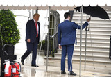 White House Photo - An aide holds an umbrella for United States President Donald J Trump as he departs the White House Saturday June 20 2020 in Washington DC Trump is attending a Make America Great Again campaign rally in Tulsa Oklahoma the first since the outbreak of the coronavirus pandemic postponed much of his 2020 reelection campaign last spring  Credit Mike Theiler  Pool via CNPAdMedia