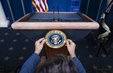 Mark Andes Photo - Communications staff installs the presidential seal on the lectern prior to President Donald Trump delivering remarks on the stock marked and the Dow reaching 30000 for the first time in history at the White House in Washington DC on Tuesday November 24 2020Credit Kevin Dietsch  Pool via CNPAdMedia