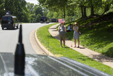 American Flag Photo - Pedestrians hold an American flag as the Presidential motorcade carrying United States President Donald J Trump departs the Trump National Golf Club in Sterling Virginia for the White House in Washington DC US on Saturday May 23 2020  Credit Stefani Reynolds  CNPAdMedia